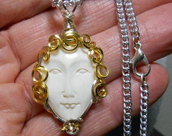 Whimsical carved face cabochon pendant, natural bone, from Indonesia, hand wrapped silver and gold filigree setting.