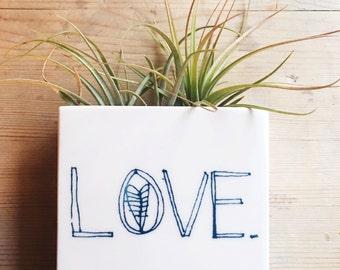 small porcelain planter / wall vase screenprinted blue text LOVE.