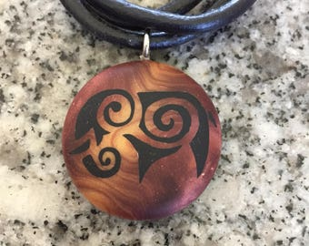 Tribal Elephant hand carved on a polymer clay bronze/light gold color background. Pendant comes with a FREE necklace