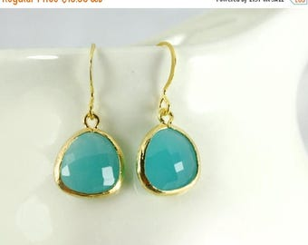 20% off. Aqua blue earrings opaque-ish with gold bezel setting. Framed and faceted