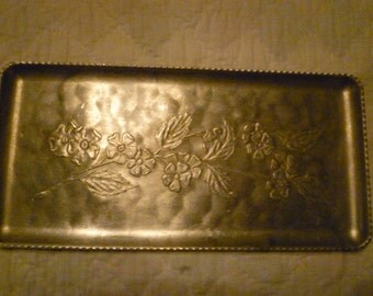 Aluminum tray with a raised design of Dogwood flowers and leaves.
