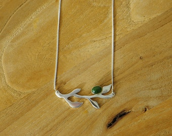 Silver necklace with jade in a gold zetkast.