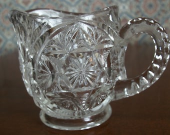 Antique Clear Cut Glass Small Creamer on a Pedestal with a Star and Floral Pattern – Notched Handle