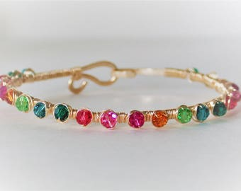 A rainbow of round swarovski crystals wire wrapped with 14ct gold filled wire onto 14ct gold filled bracelet