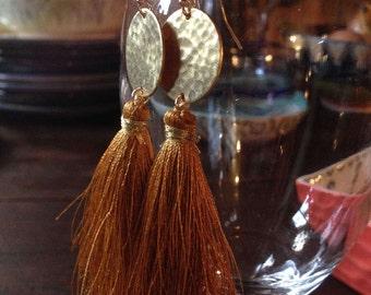 Silk tassel earrings on hammered brass discs. Brassy gold tassel danglingling from a hammered brass disc. A beautiful rick color match.