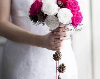 winter bridal bouquet made of stabilized roses and pinecones