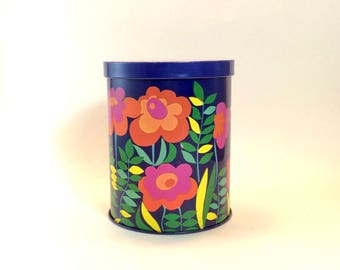 Deep blue seventies storage tin or canister with flower power decor and orange lid. Stockage d'étain rétro bleu.