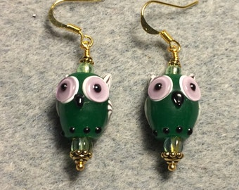 Dark green lampwork owl bead earrings adorned with green Czech glass beads.