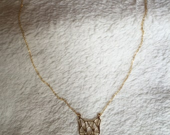 Ornate gold chain necklace of a tiger head pendant