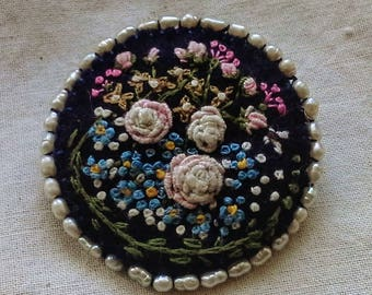 Roses and cottage garden flowers on a blue felt brooch