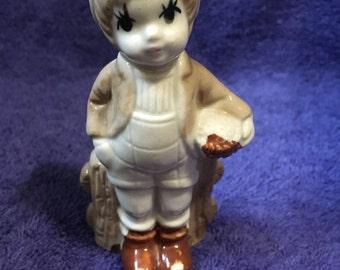 Vintage Porcelain Boy Figurine at fence carrying a basket