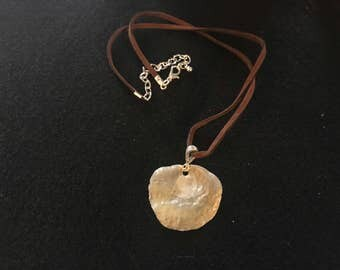 Handcrafted jingle shell pendant necklace.
