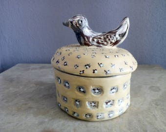 Clay box with bird on top