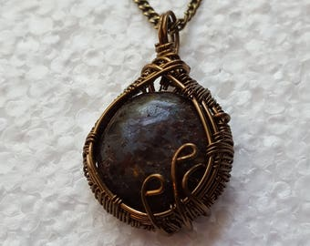 Antiqued wire wrapped speckled black cabochon with antiqued copper chain.