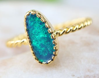 Australian opal ring in royal blue of green fire in prongs setting with 18k gold twist band