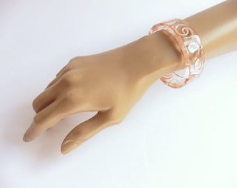 1950s palest pink-tinged clear lucite bangle adorned with white curlicues