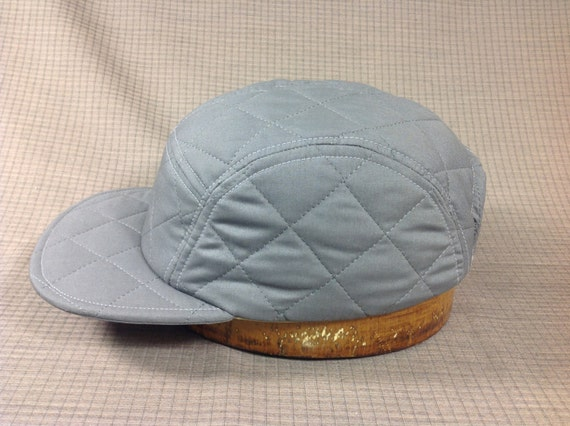 Grey cotton quilted fabric, 5 panel adjustable cap. Fitted available upon request. Leather or cotton sweatband