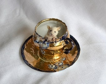 Taxidermy mouse in fancy tea cup.