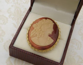 A fine oval cameo vintage jewelry brooch with a goldtone metal mount set with a glass mixed colour cameo of the classical young maiden