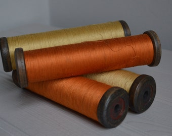 Rustic antique wooden bobbin with gold or orange thread