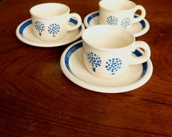 Threevintage earthenware cups and saucers by Elsterwerda DDR (GDR), cream coloured with blue. Design: trees consisting of blue hearts