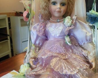 Cathay collectible doll  porcelain fairy on a swing blond haired blue eyes.