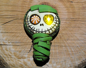Advocado green baby mummy. Creepy and cute skull with asymmetric eyes: one candy and one heart. Citric colors. Brooch or magnet