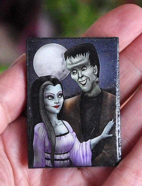 Broche Herman y Lily Munster