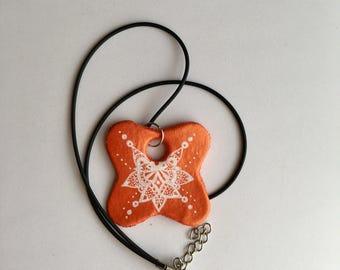 Handmade orange necklace with white pattern detail