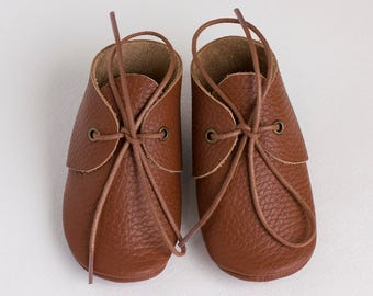 Brown baby moccasins with shoe laces. Newborn, infant, toddler shoes
