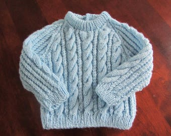 Blue baby sweater with cables
