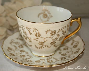 Coalport, England: Tea cup and saucer, white and gold