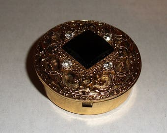 Gold Tone Metal Pill Box with Rhinestones and Black Gem.
