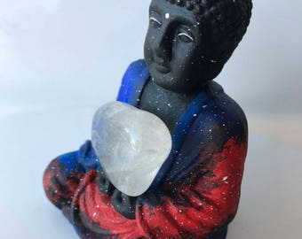Meditating Buddah holding a clear quartz crystal