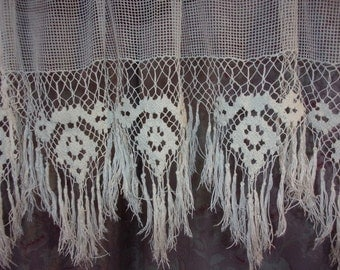 A pair of curtains made in fabric and old lace