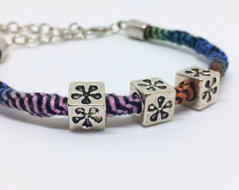 Multicolored spiral macrame bracelet with metal flower beads