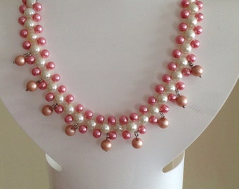 Necklace with pink and white glass pearls.  Adjustable length - one size fits all - no metal clasps