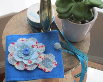Hand sewn Blue felt needlecase with applique flower and button fastening