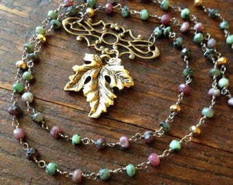 Antiqued gold leaf necklace with a brass centerpiece and ruby ziosite rosary chain.