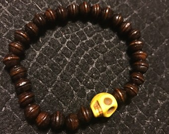 Wooden beaded stretch bracelet with yellow skull charm
