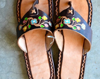 Traditional style sandals with flowers and designs.