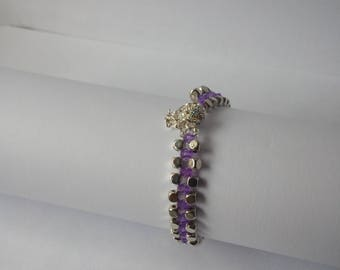 A purple and silver cubed beaded bracelet with clear crystals on a silver plated magnetic clasp with a safety chain