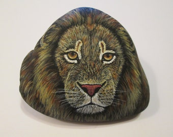Lion Portrait hand painted on a rock by Ann Kelly