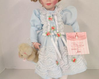 "Vintage porcelain curly blond hair blue eyed "" Julie"" doll 15 inch blue dress with teddy bear  Collectible Memories used"