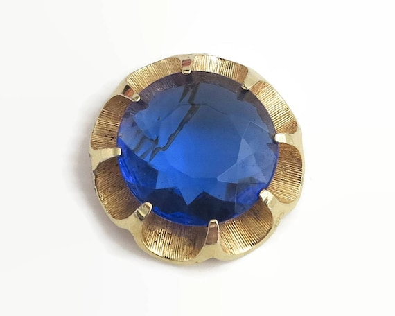Large flower brooch with huge faceted circular blue glass stone in prong setting, gold tone metal setting, rollover clasp, circa 1970s