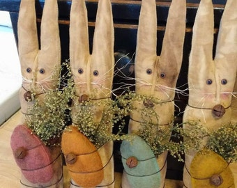 Primitive stick bunnies there ten inches tall by 2 inches wide it's wrapped with Sweet Annie and has I felt wool egg