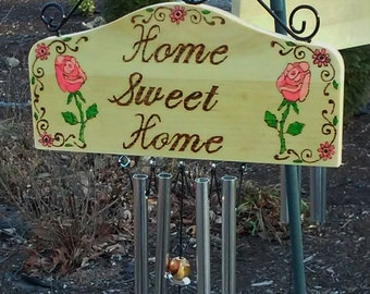 """Wind chimes wood burned sign with """"Home Sweet Home""""  on it with painted pink roses"""