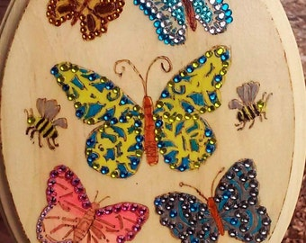 Wood burned and painted oval wall decor with bees and blue, yellow and pink butterflies embellished with crystals