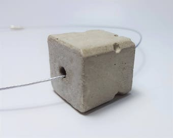 Concrete cube with stainless steel necklace