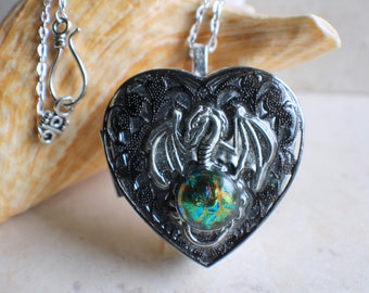 Dragon music box locket, heart shaped locket with music box inside, in  silvertone with dragon and silver filigree on front cover.